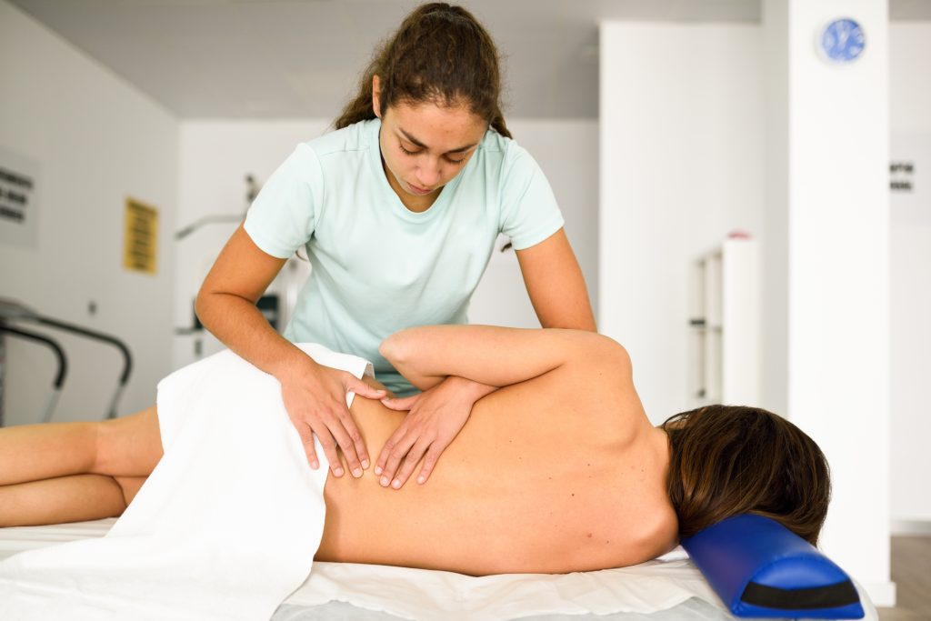 professional female physiotherapist giving lumbar shoulder massage woman